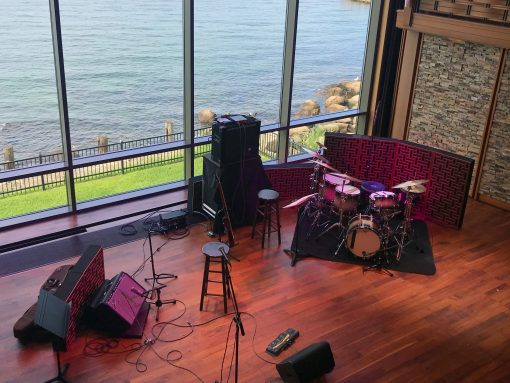Impression Pro Series Bass Traps standing behind drumset and amplifier with view of water