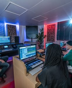 School of Electronic Music in Manchester, UK with Students in Midi Studio with Alpha Pro Series Acoustic Panels on walls in 2D(a) Gray Elm veneer with black fabric