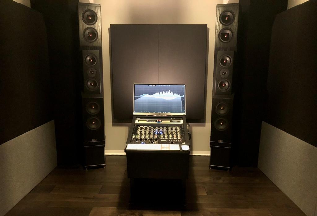 Mastering studio with GIK Acoustics Soffit Bass Traps, 244 Bass Traps in standard black fabric behind speakers.